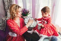 一个年轻母亲在屋子里显示她一岁的女儿在窗口基石的一个时钟 妈妈和女儿红色礼服的 免版税库存图片