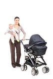 一个年轻母亲的全长画象有婴孩和pushcha的 库存照片