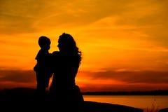 一个年轻母亲的剪影有她的小孩的 免版税图库摄影