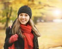 一个年轻浅黑肤色的男人在温暖的红色秋天穿衣 图库摄影
