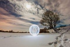 一个冻湖的表面上的发光的球 免版税库存照片
