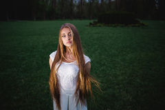 一个幻灯照亮的年轻白肤金发的女孩在夜奥秘庭院里 免版税库存图片