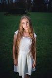 一个幻灯照亮的年轻白肤金发的女孩在夜奥秘庭院里 库存图片
