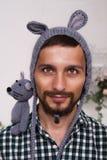 一个年轻爸爸的画象儿童` s帽子的有耳朵和一只老鼠的在他的肩膀 免版税库存照片
