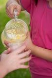 从一个玻璃投手的女孩倾吐的柠檬水 库存照片