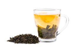 一个玻璃杯子在白色背景隔绝的有很多绿茶 一个美丽的杯子用柠檬和自然绿色茶叶 复制空间 库存照片