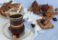 一个玻璃杯子强的红茶,切片饼,肉桂条、薄酥饼和块菌状巧克力在一张轻的桌布 免版税库存图片