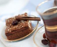 一个玻璃杯子强的红茶,切片饼,肉桂条、薄酥饼和块菌状巧克力在一张轻的桌布 免版税图库摄影
