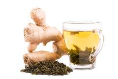 一个玻璃杯子有很多绿色有机茶 在白色背景和姜隔绝的茶杯 一个美丽的杯子用绿色茶叶 免版税图库摄影