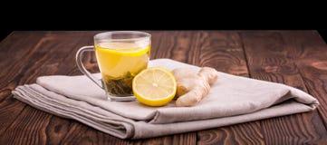 一个玻璃杯子有很多黄色饮料 在一张黑暗的木桌上的一个杯子 一个美丽的杯子用被切的柠檬和有机姜根 库存照片