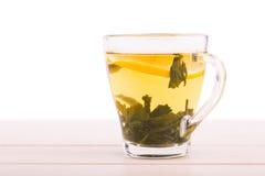 一个玻璃杯子有很多绿茶 在一张轻的木桌上的一个杯子 一个美丽的杯子用柠檬和自然绿色茶叶 复制空间 免版税库存照片