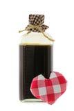一个玻璃瓶在褐色的媚药与红色方格花布心脏 免版税库存图片