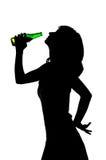 女孩饮用的啤酒,剪影 免版税库存图片