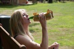 从一个玻璃瓶的妇女饮用的酒精在纸袋 免版税库存图片