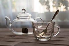 一个玻璃茶罐用花中国茶准备好酿造和在木背景的一个盖帽在窗口前面 库存照片