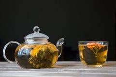 一个玻璃茶罐用花中国茶和绿茶盖帽在木桌上的在黑暗的背景前面 免版税库存图片