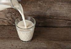 从一个玻璃水瓶的倾吐的牛奶到玻璃里 库存照片