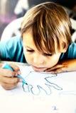 一个年轻男孩做着图画 库存照片