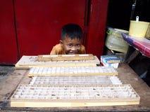 一个年轻男孩卖用于蜘蛛战斗的各种各样的蜘蛛 免版税库存照片