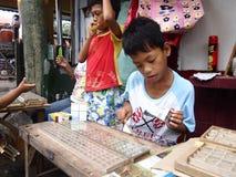 一个年轻男孩卖用于蜘蛛战斗的各种各样的蜘蛛 免版税图库摄影