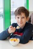 一个年轻男孩吃牛奶奶油甜点用被切的果子 免版税库存照片