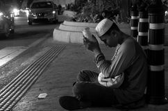 一个年轻男孩在吉隆坡坐乞求金钱的 库存图片