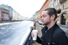 一个年轻男孩在有一杯的城市附近走咖啡 免版税图库摄影