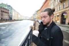 一个年轻男孩在有一杯的城市附近走咖啡 免版税库存图片