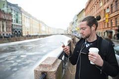 一个年轻男孩在有一杯的城市附近走咖啡 库存图片
