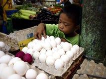 一个年轻男孩安排在盘子的新鲜的鸡蛋在一个公开市场上 免版税图库摄影