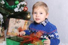 一个年轻男孩的画象在孩子后的圣诞树 免版税库存图片