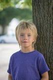 一个年轻男孩的画象在树前面的 库存照片