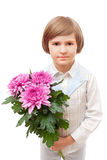 一个年轻男孩站立与延命菊花束  免版税库存图片