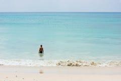 一个年轻男孩站立在海洋岸 免版税图库摄影
