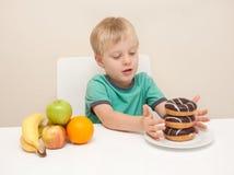 一个年轻男孩考虑他是否将食用一个不健康的多福饼 免版税库存照片