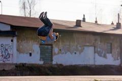 一个年轻男孩跳在街道上的翻筋斗 图库摄影