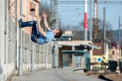 一个年轻男孩跳在街道上的翻筋斗 免版税库存照片
