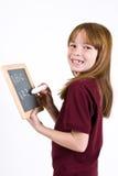 在粉笔板的年轻学校女孩文字 免版税库存图片