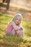 一个年轻白肤金发的女孩坐在后面光的草在su 免版税库存照片