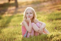 一个年轻白肤金发的女孩坐在后面光的草在su 免版税库存图片