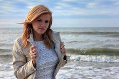 一个年轻白肤金发的女孩的画象夹克的,摆在反对背景海挥动 免版税库存照片