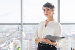 一个年轻确信的女性办公室经理的特写镜头画象她的工作场所的,为做企业任务准备 库存照片