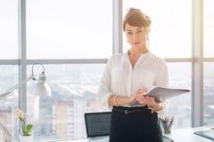 一个年轻确信的女性办公室经理的特写镜头画象她的工作场所的,为做企业任务准备 免版税库存图片