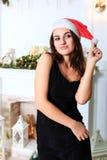 一个黑礼服和圣诞老人` s帽子的快乐的女孩 免版税库存照片