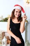 一个黑礼服和圣诞老人` s帽子的快乐的女孩 库存照片