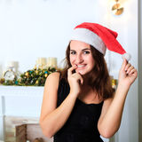 一个黑礼服和圣诞老人` s帽子的快活的女孩 图库摄影