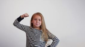 一个滑稽的女孩握紧她的显示力量的拳头 女孩仿效大力士 股票视频