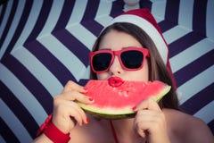 一个滑稽的女孩的画象在圣诞老人帽子和红色太阳镜 库存照片