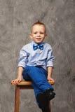 一个滑稽的小男孩的画象坐一把高凳子 免版税库存照片
