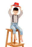 一个滑稽的小男孩的画象坐在红色的一把高凳子 库存照片